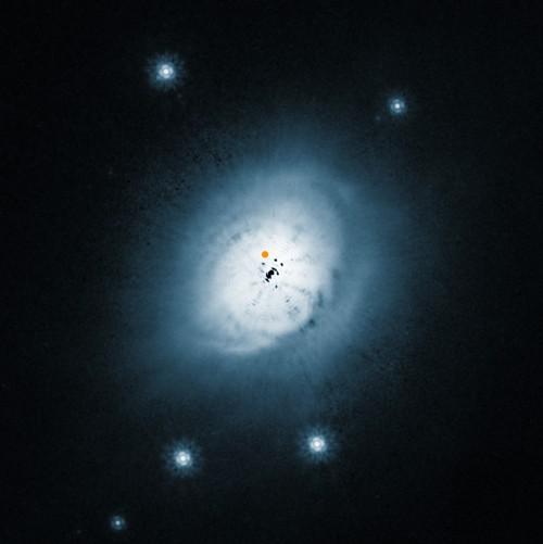 Der Stern HD 100546 und seine Scheibe, aufgenommen mit dem Hubble-Teleskop. Der orange Punkt zeigt an, wo sich der Planet befindet (Bild: ESO/NASA/ESA/Ardila et al.)