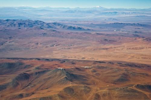 Die Gegend um den Cerro Armazones. In der Bildmitte erkennt man den Cerro Paranel mit den vier großen VLT-Teleskopen der europäischen Südsternwarte. Links dahinter ist der Gipfel des Cerro Armazones zu sehen (und weit im Hintergrund der 6720 Meter hohe Gipfel des  Vulkans Llullaillaco) Bild: ESO