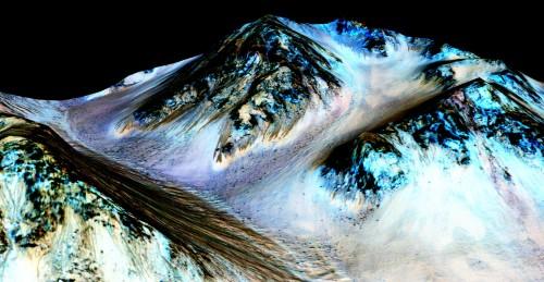 Darstellung der Daten mit denen die aktuellen Ergebnisse gewonnen wurden. Das Bild ist keine echte Aufnahme sondern  zeigt Falschfarbenaufnahmen die über ein digitales Modell der Marsoberfläche gelegt wurden. Die Höhenunterschiede sind verzerrt dargestellt um die interessanten Details besser sichtbar zu machen. Die Rinnen, die durch kürzlich fließendes Salzwasser entstanden sind, sind in schwarz im linken Teil des Bildes zu sehen (sie sind ca. 100 Meter lang). Bild: NASA/JPL/University of Arizona