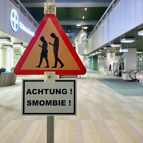 Dass Technik nicht nur eine tolle Errungenschaft ist, sondern irgendwie auch etwas mit uns Menschen anzustellen scheint, illustriert zumindest dieses Schild in Berlin. (Urheber:  A_Peach, Lizenz: Creative Commons)