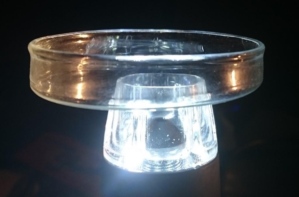 Das USB-Mikroskop als Inverses Mikroskop um den Wassertropfen von unten zu filmen. Das weiße leuchten kommt von den acht LEDs des Mikroskops selbst, der gelbe Schein von einer Taschenlampe, die von der Seite leuchtet